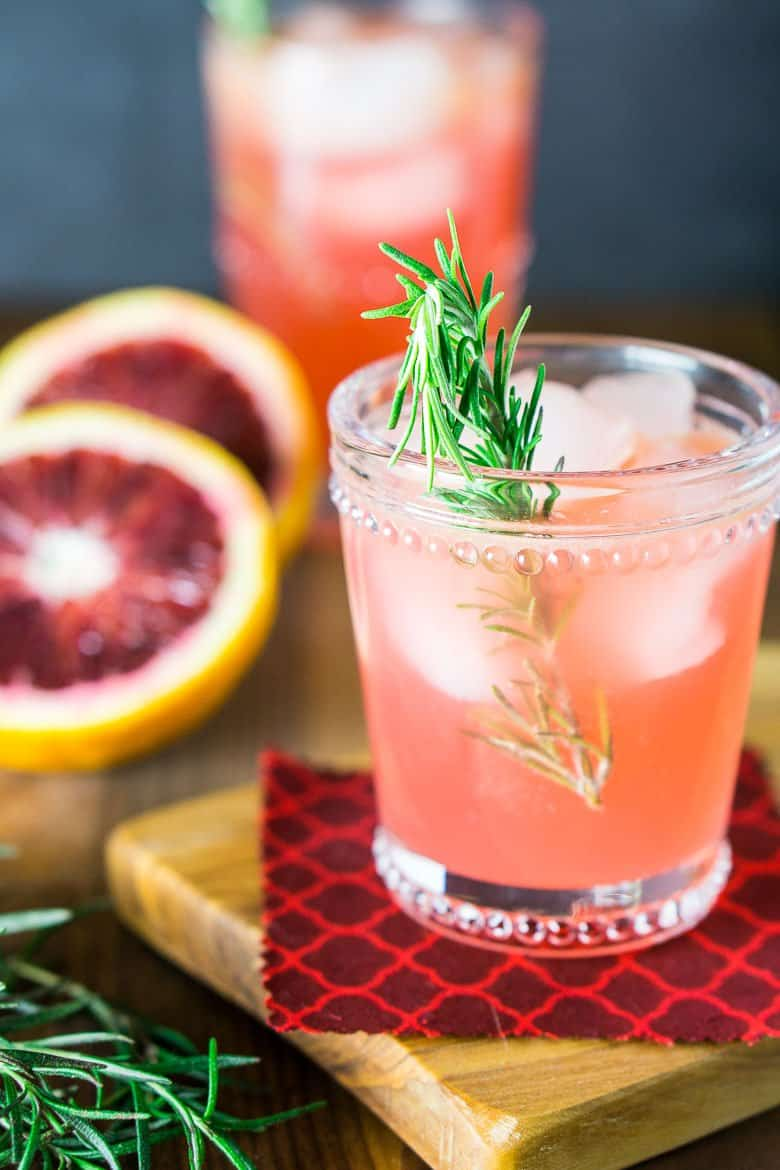 A blood orange rosemary gin and tonic on a wooden board with fresh citrus.