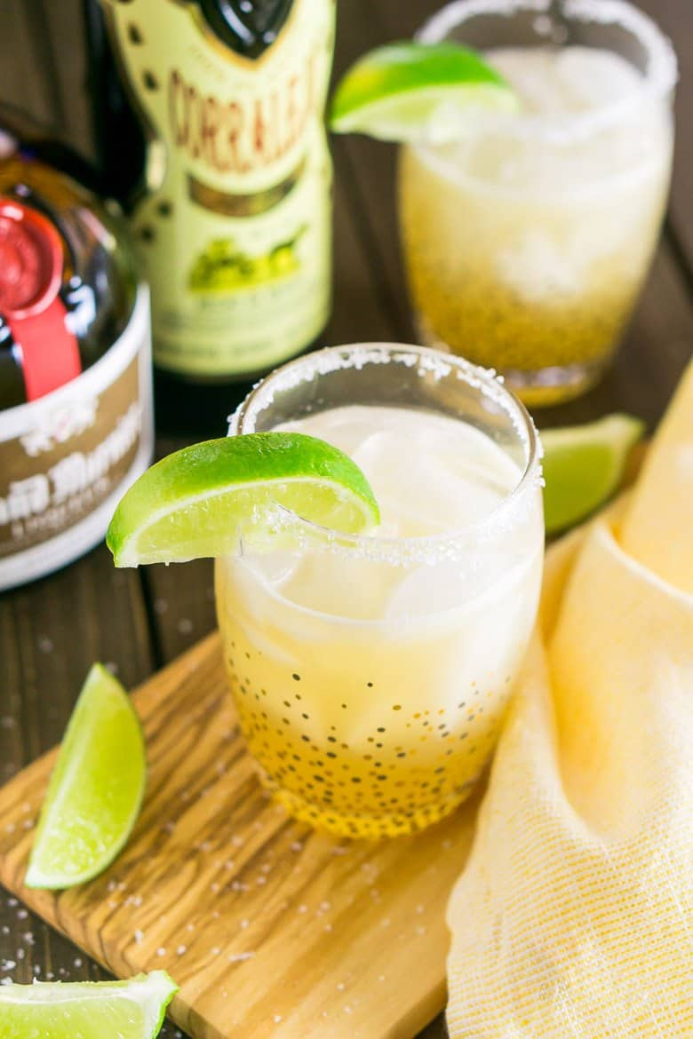 A classic margarita on a wooden board with limes.