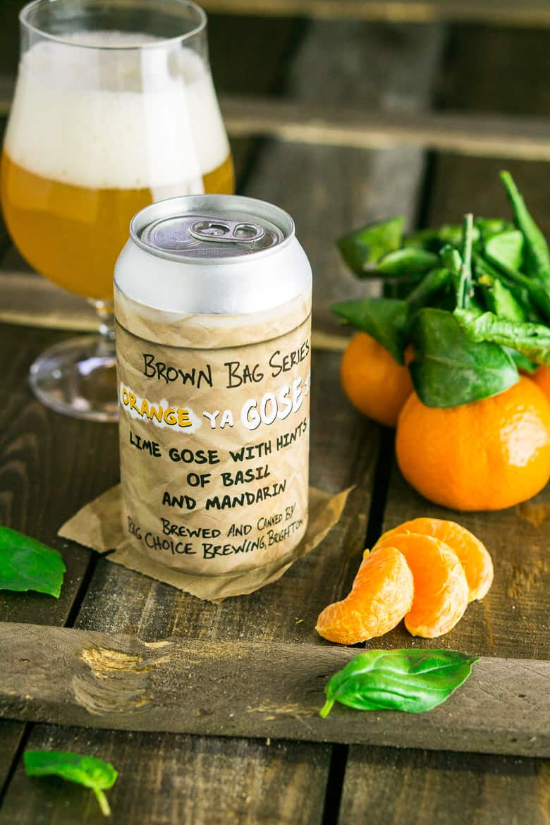 A can of Gose on a wooden board with a peeled mandarin next to it.