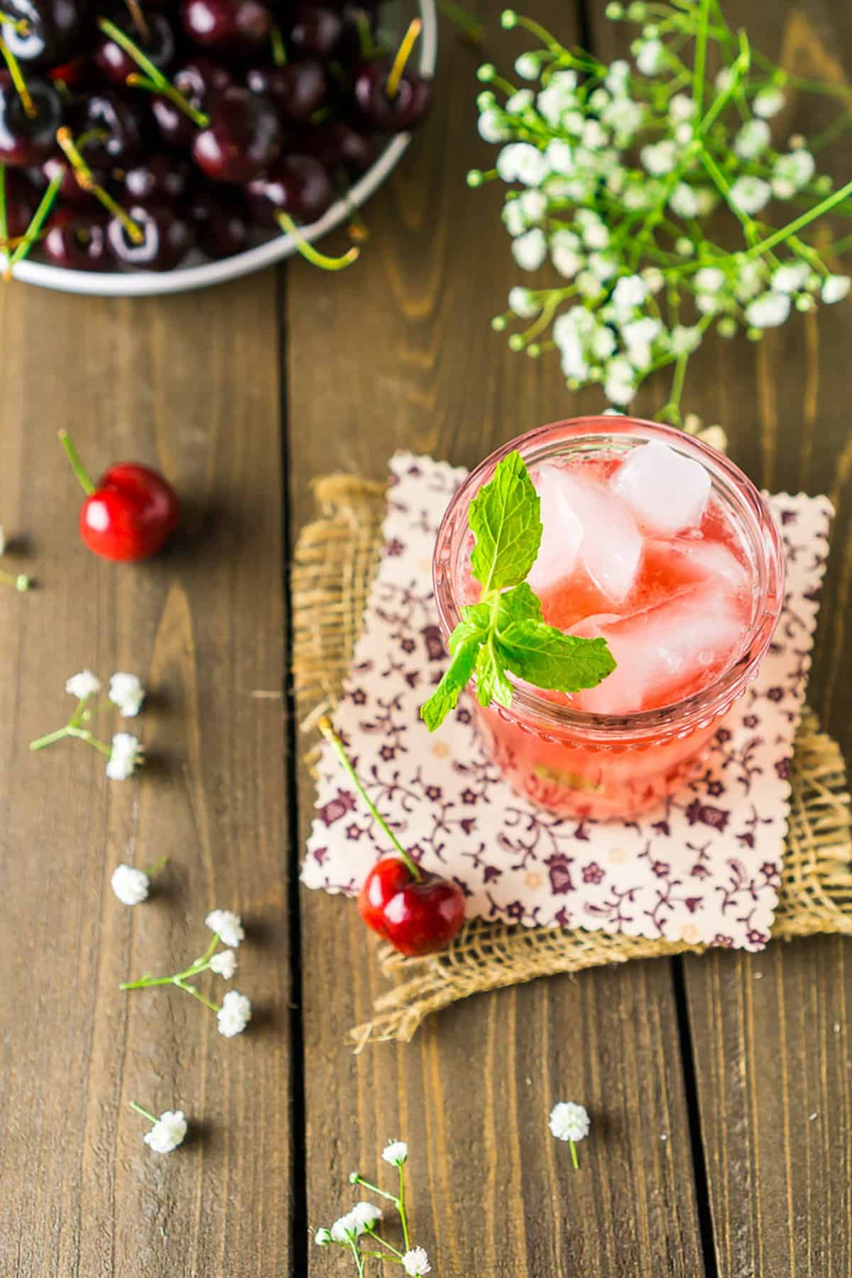 An aerial view of a cherry bourbon smash with fresh cherries around it.