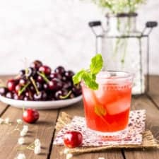 A cherry bourbon smash on burlap with a plate of cherries and white flowers in the background.