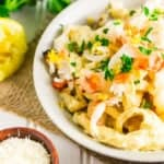 A bowl of grilled lobster Alfredo with Parmesan, lemons and parsley on the side.