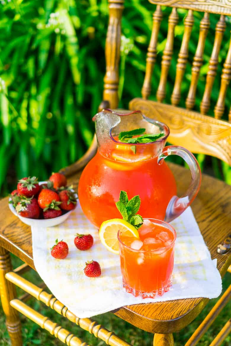 Looking down on a vintage chair with the strawberry lemonade in a pitcher.
