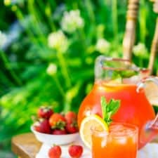 A pitcher of minted strawberry lemonade on a wooden chair in a garden.