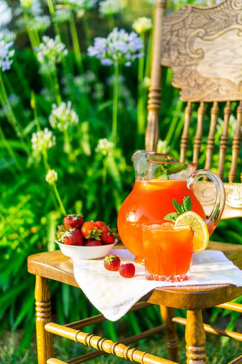 The strawberry lemonade in a pitcher on a chair with purple flower in the background.