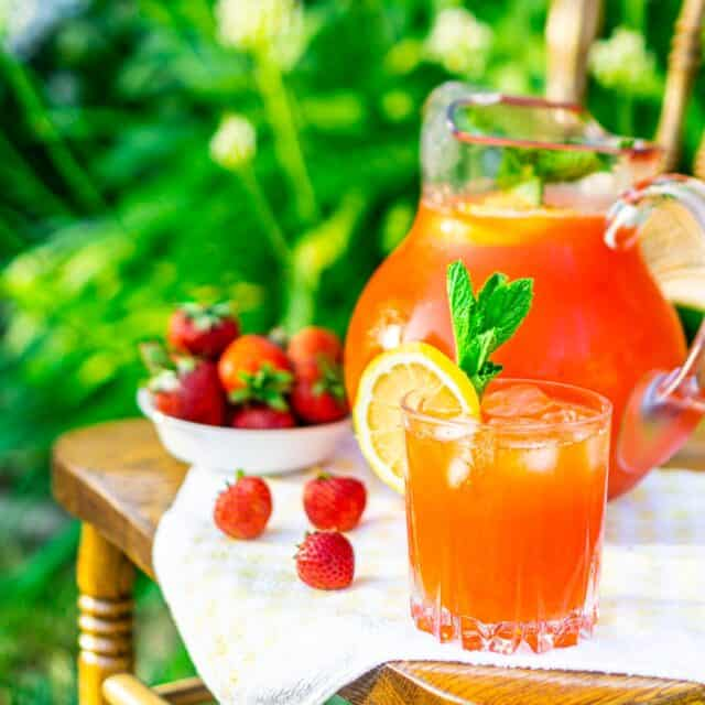 A glass of strawberrry-mint lemonade on a chair in a garden with a pitcher behind it.