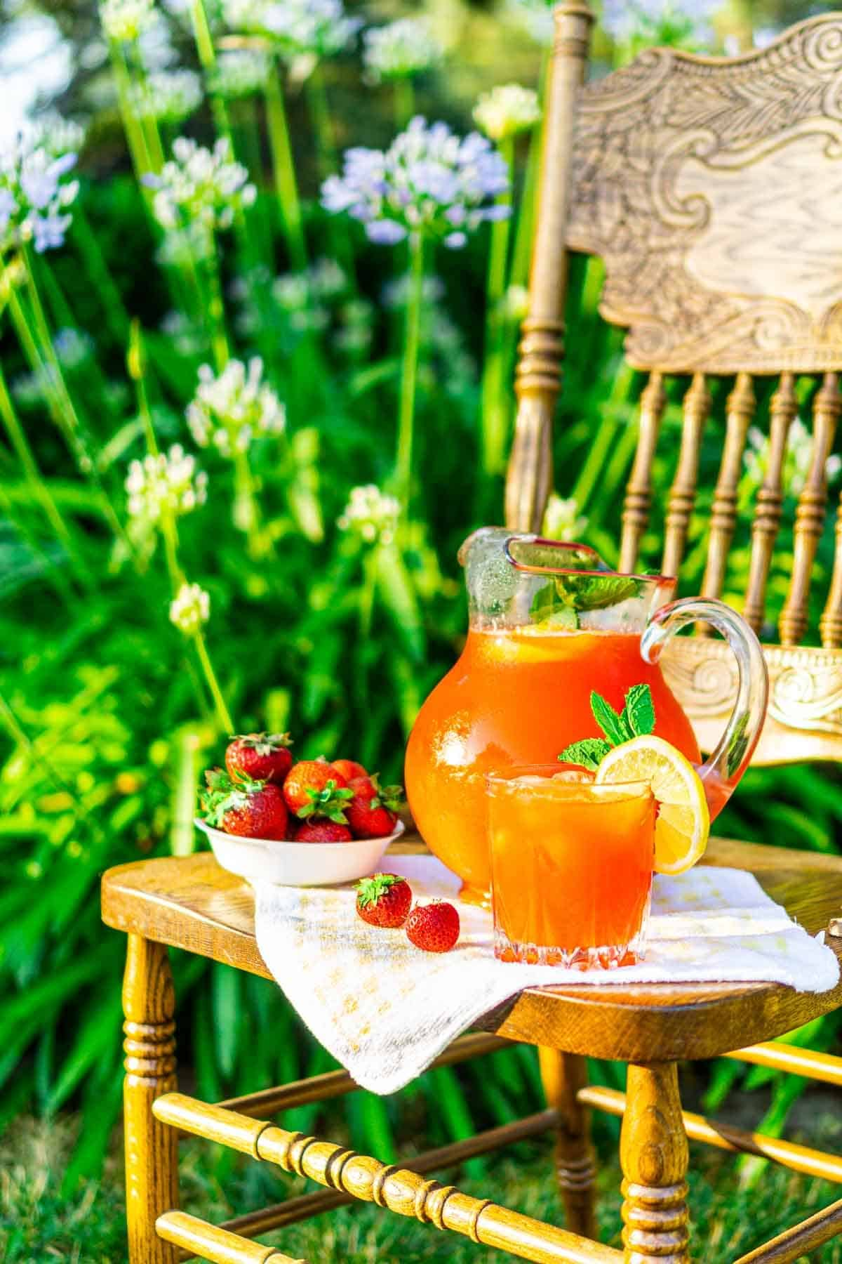 The pitcher of strawberry-mint lemonade in front of garden flowers.