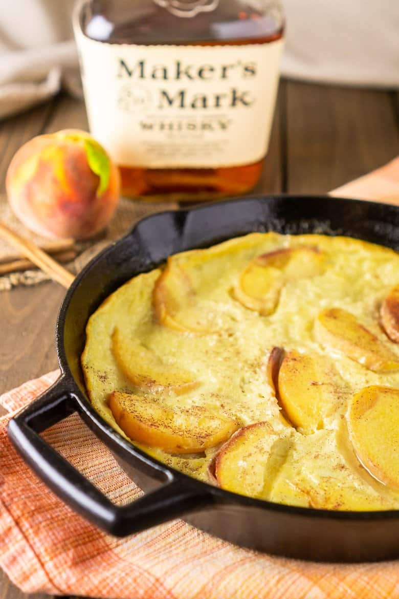 Peach clafoutis in a cast-iron skillet with a bottle of bourbon in the background.