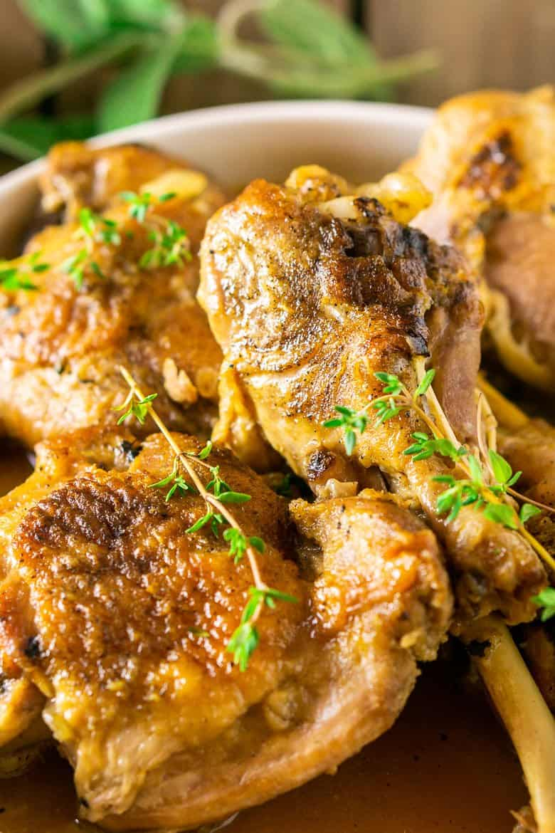 Maple-braised turkey legs and thighs with a focus on the legs on a white platter surrounded by fresh thyme.