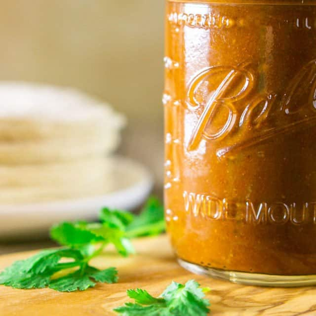 Red enchilada sauce in a mason jar surrounded by cilantro and corn tortillas.
