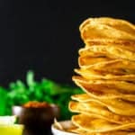 Freshly fried tostada shells stacked against a black background with cilantro, chili powder, lime and salt.