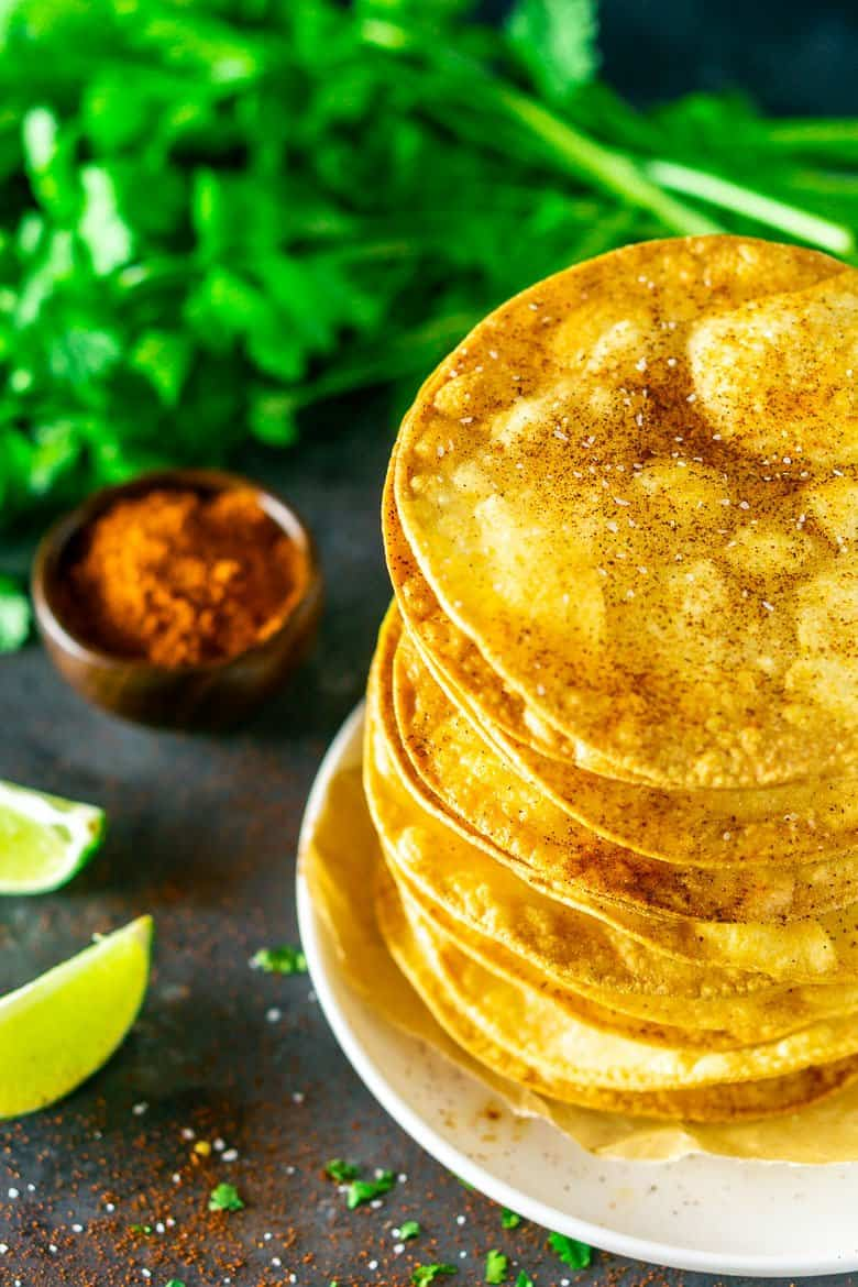 Looking down at tostada shells surrounded by cilantro, chili powder, salt and lime.
