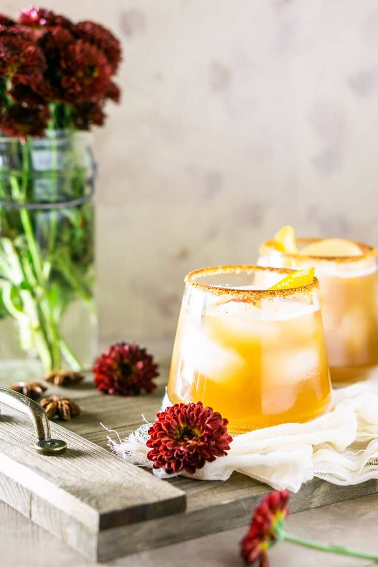 Gingered bourbon-apple cider cocktail with fall flowers and a wooden tray