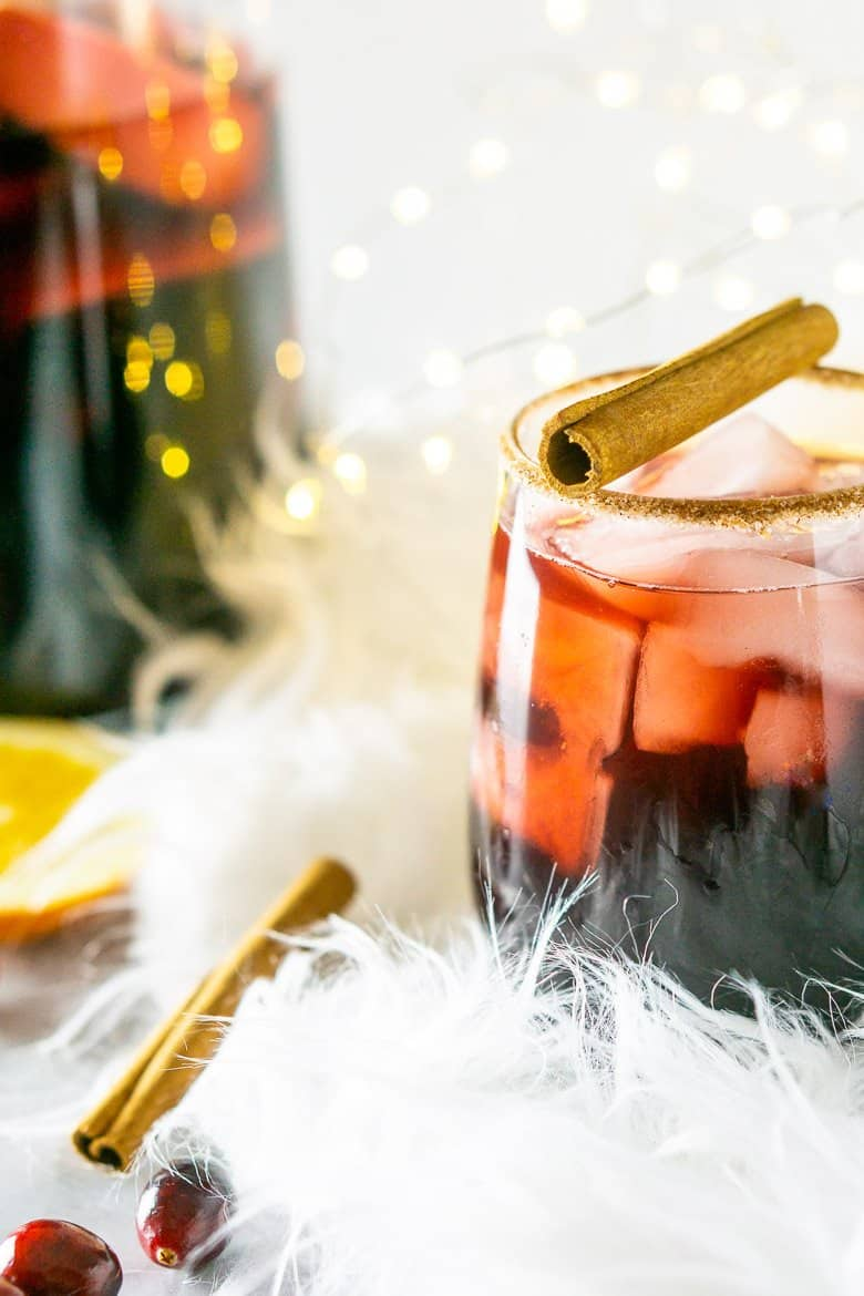 Close up of a glass of holiday sangria with a pitcher in the background.