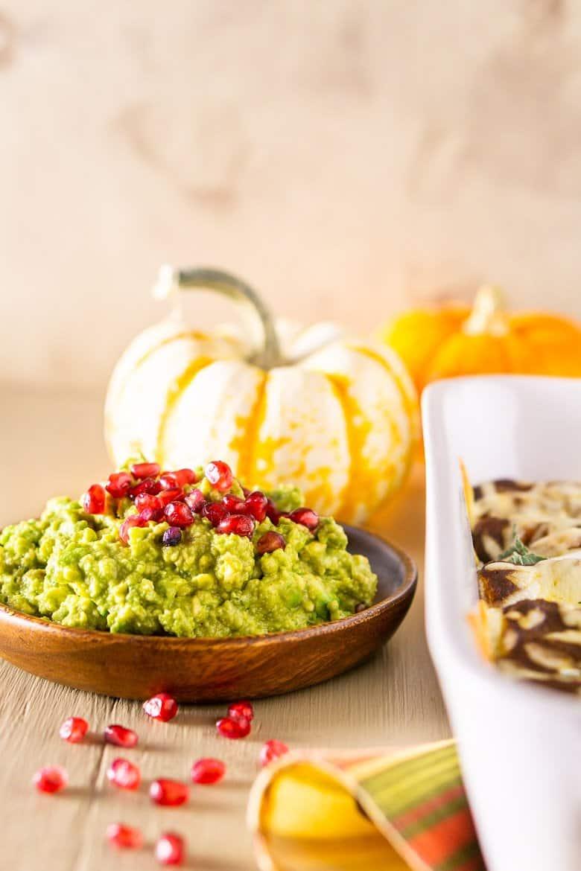 Pomegrante guacamole next to Thanksgiving enchiladas with pumpkins as decor.