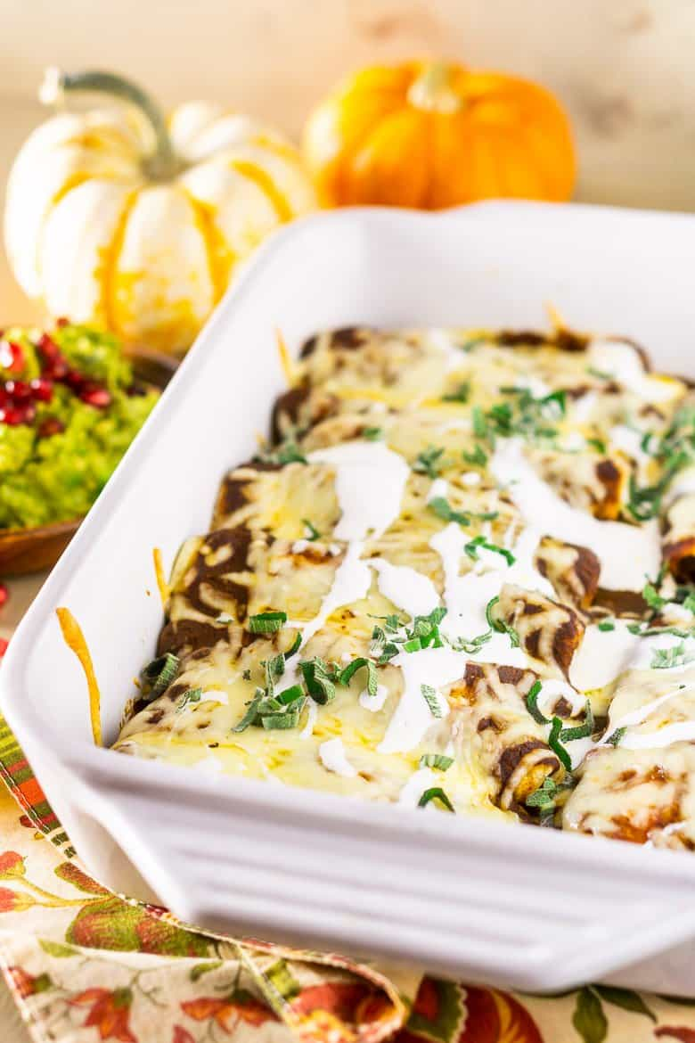 A pan of Thanksgiving enchiladas with pomegranate guacamole and pumpkins as decor.
