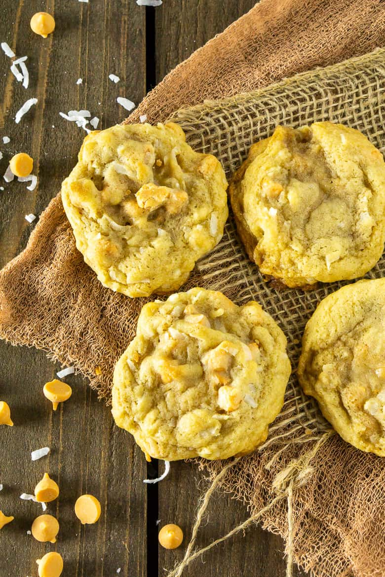 An aerial view of four butterscotch-coconut-bourbon cookies.