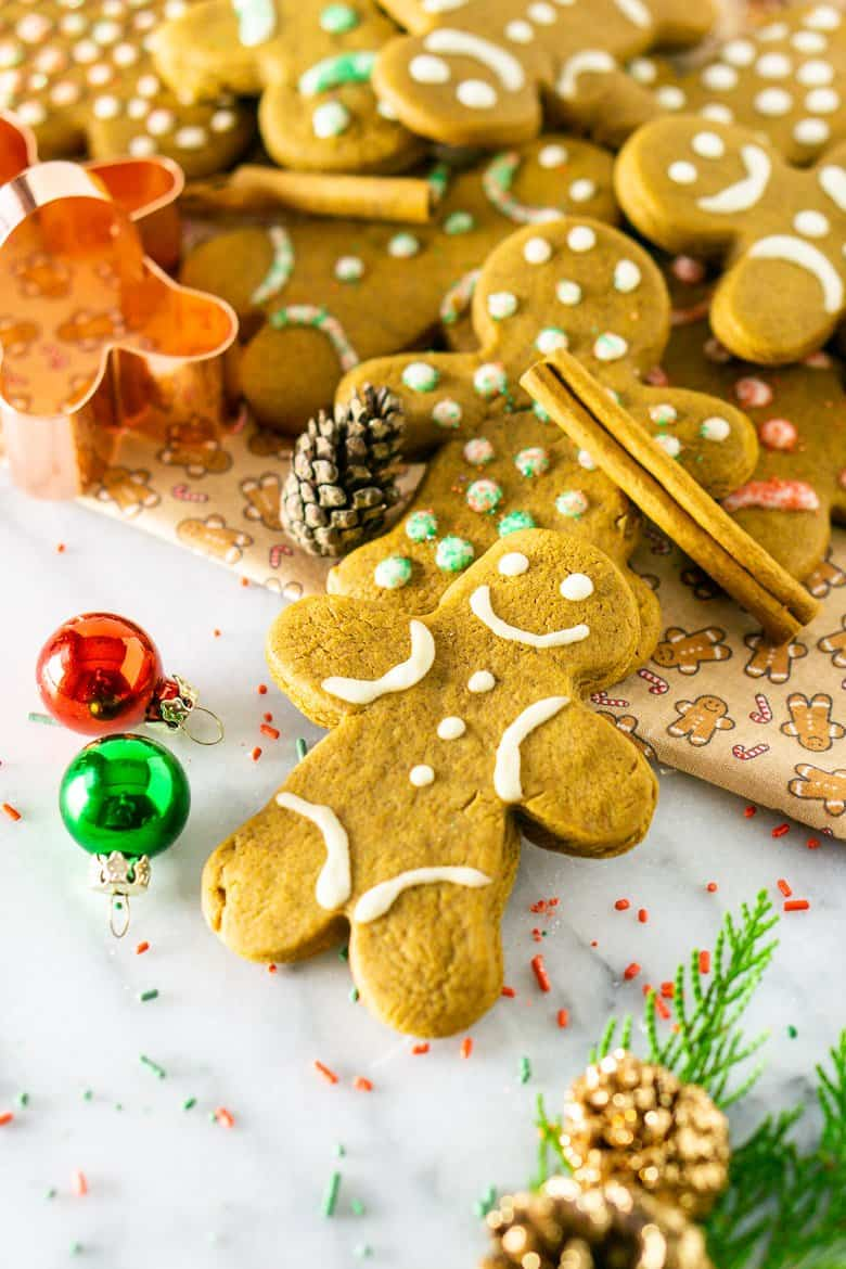 A pile gingerbread men cookies with Christmas decor and a cookie cutter.