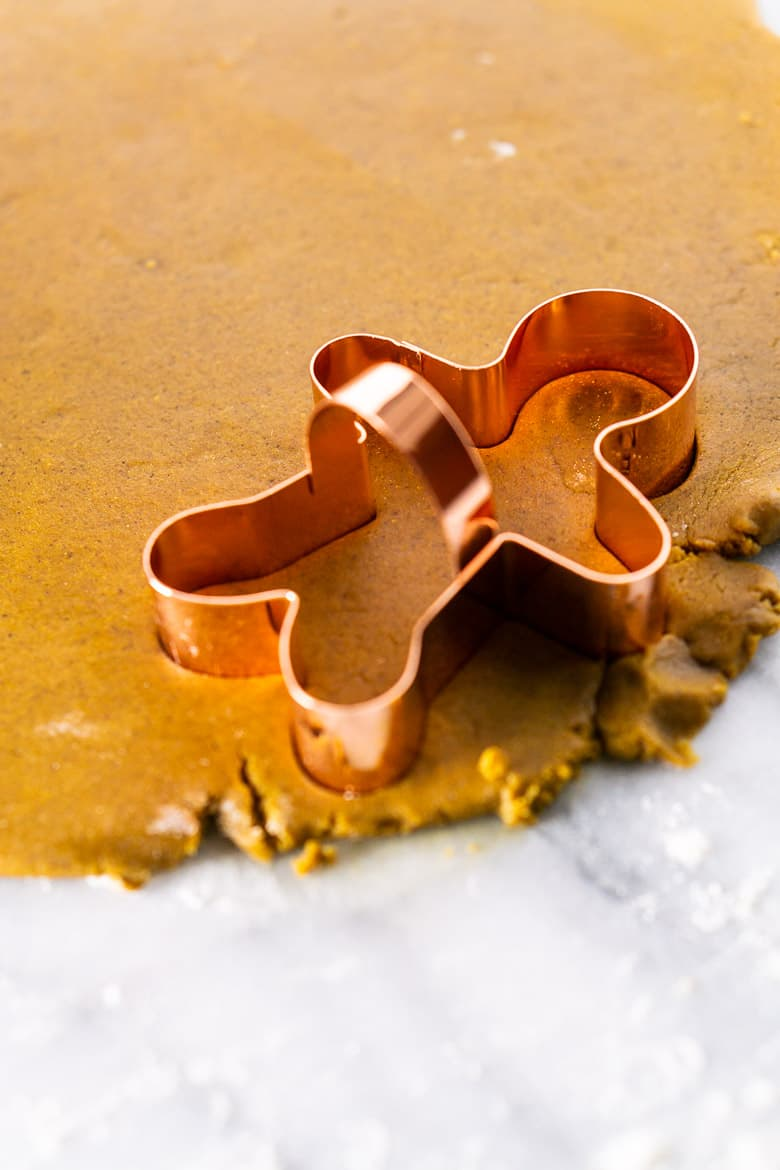 Gingerbread men cookie dough rolled out with cookie cutter.