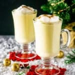 Two glasses of maple eggnog with Christmas decor.