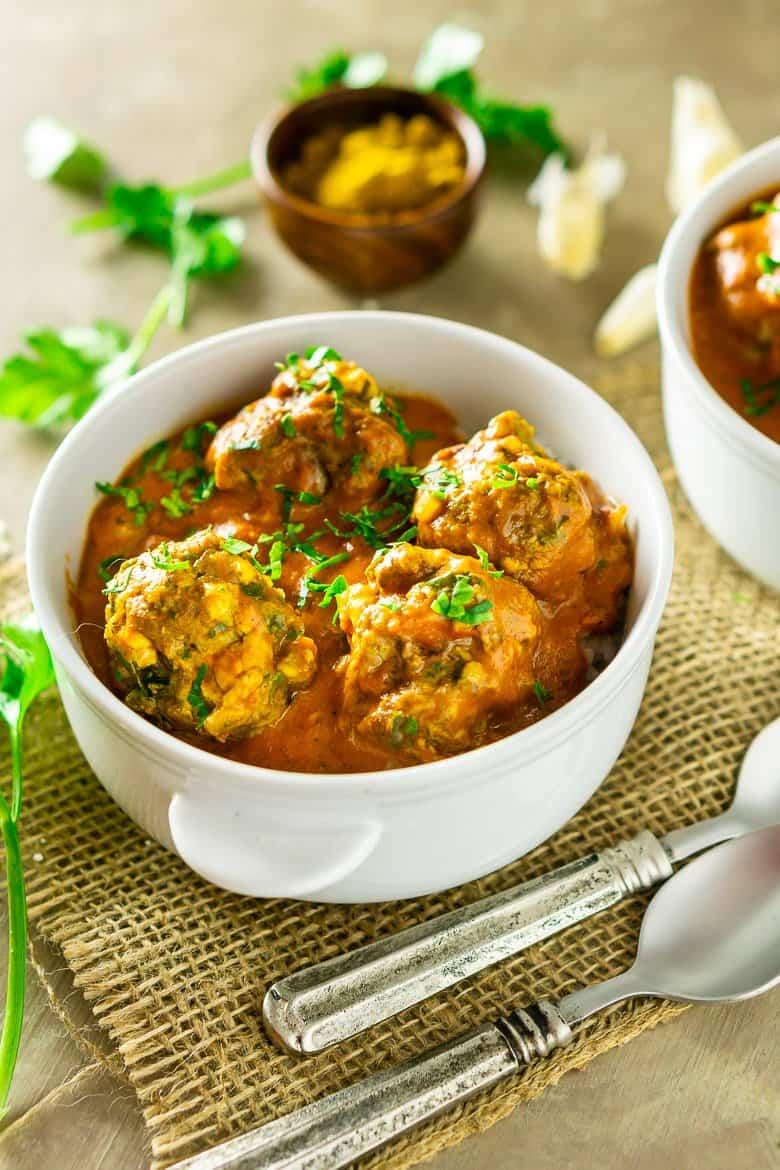 A bowl of curried feta-lamb meatballs with spoons.