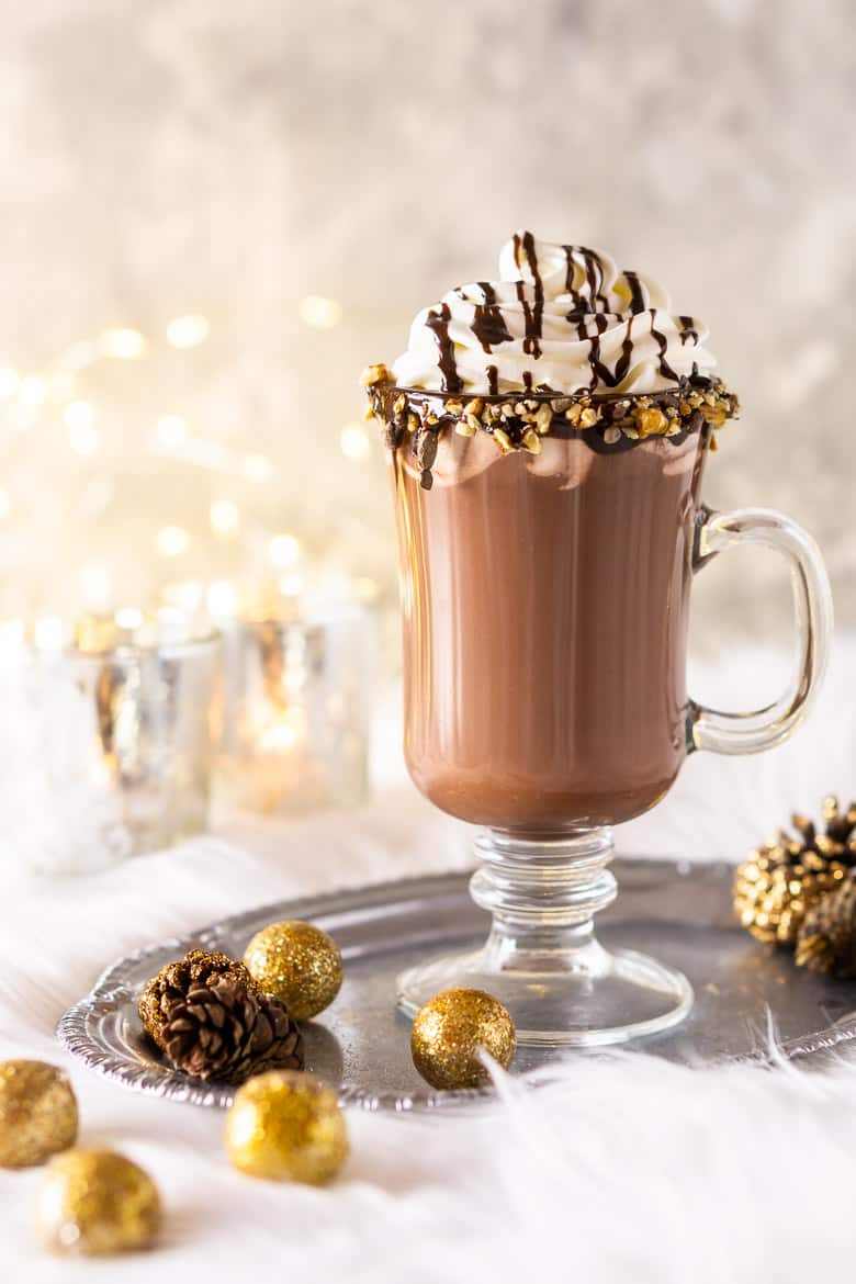 A glass of homemade hot cocoa with candles.