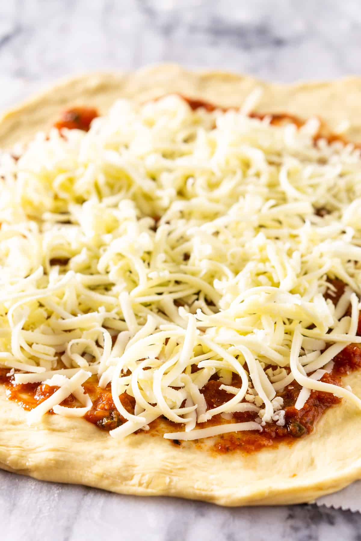 The pizza dough on a pastry board with sauce and cheese.