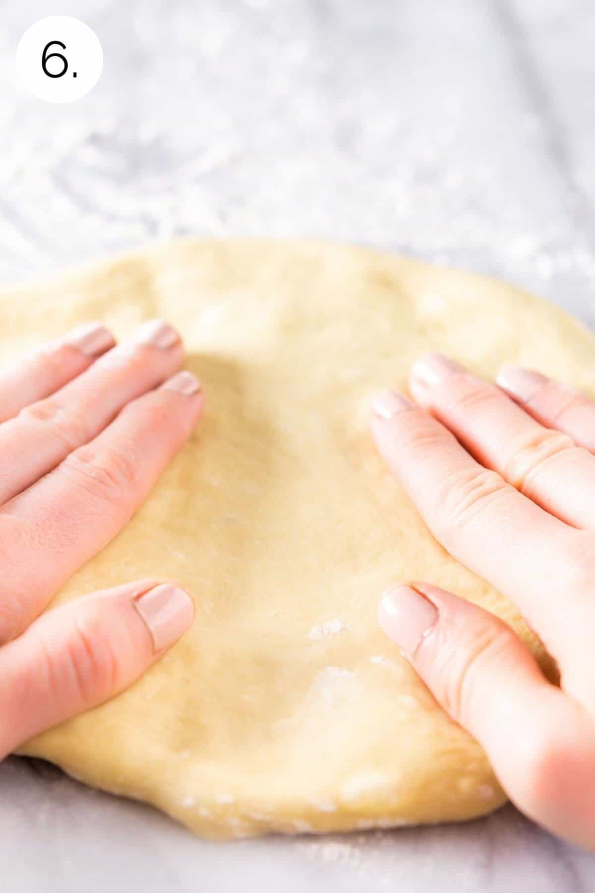 Hand-stretching the dough with the beds of fingertips on a lightly floured pastry board.
