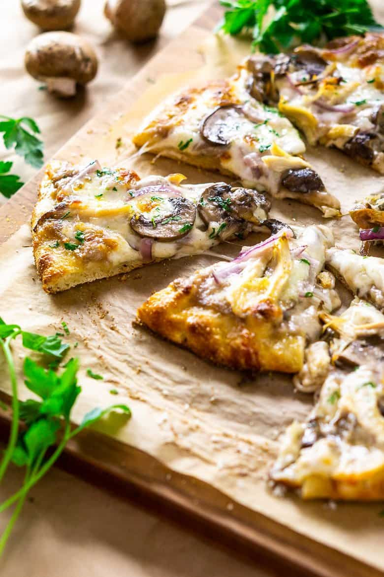 Several slices of the coq au vin pizza on a cutting board.