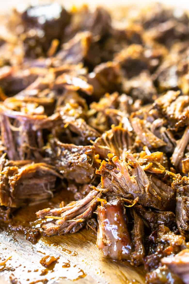 The beer-braised Mexican shredded beef on a wooden cutting board after being shredded.