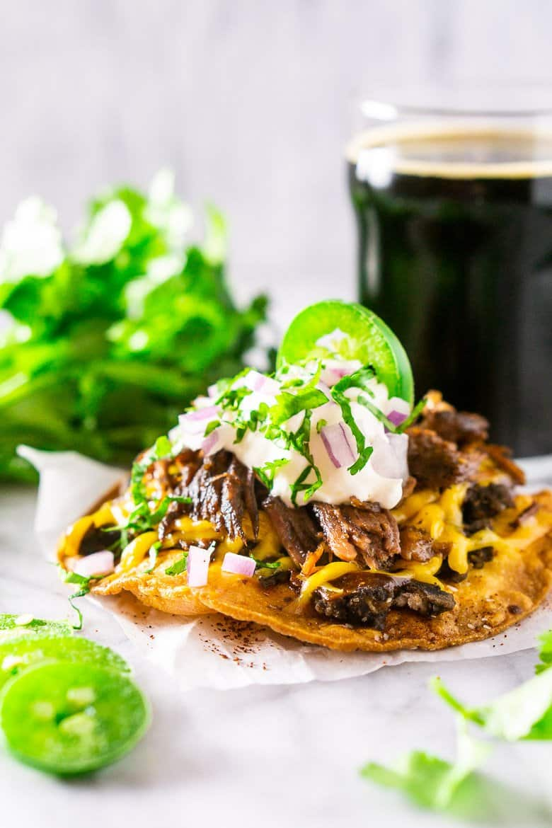 A closeup of the beer-braised Mexican shredded beef on a tostada.