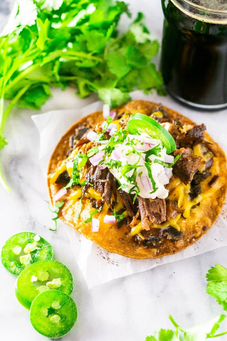 An aerial view of the beer-braised Mexican shredded beef on a tostada.