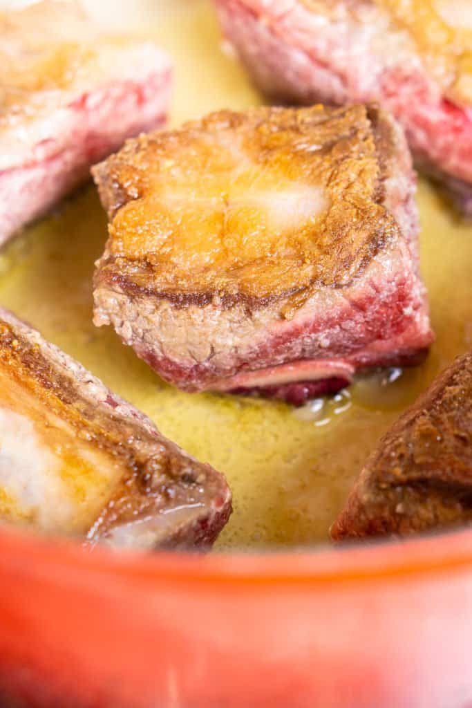 The short ribs in a Dutch oven after being browned on one side.