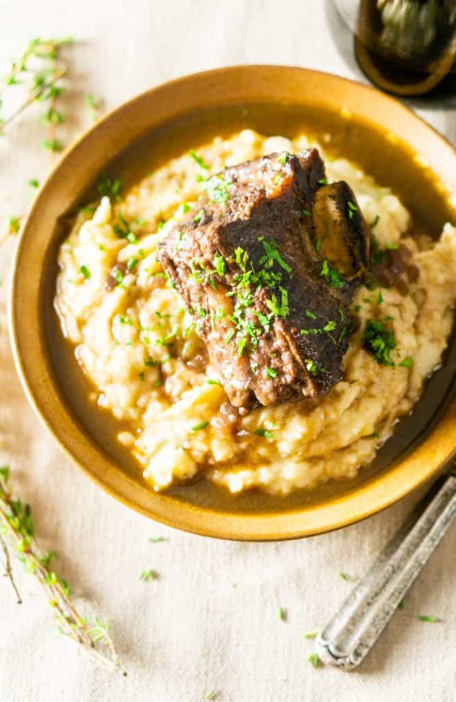An aerial shot of the red wine-braised short ribs in a bowl of mashed potatoes.