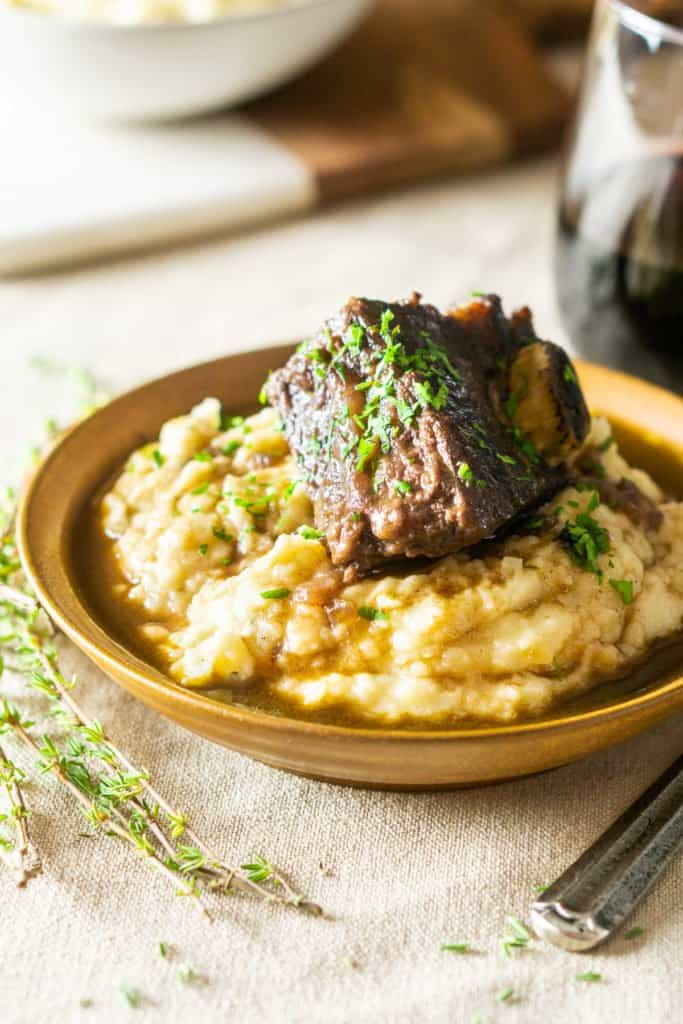 A red wine-braised short rib on mashed potatoes with a glass of wine next to it.