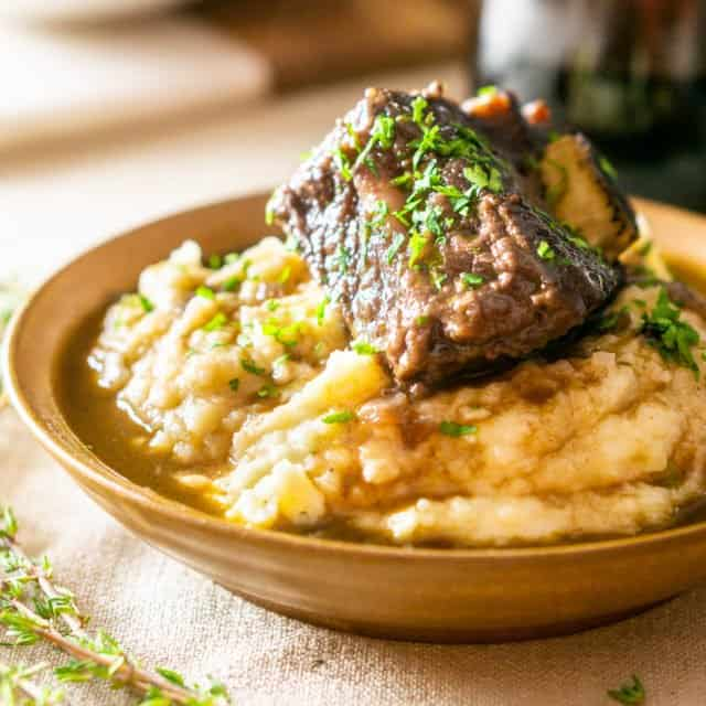 A bowl of brown butter mashed potatoes with a red wine-braised short rib on top with a glass of wine.