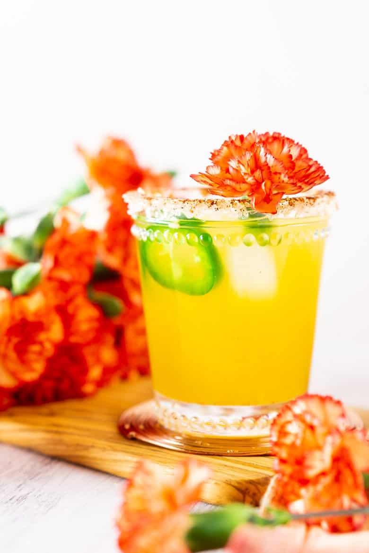 A single jalapeno-mango margarita with flowers all around.