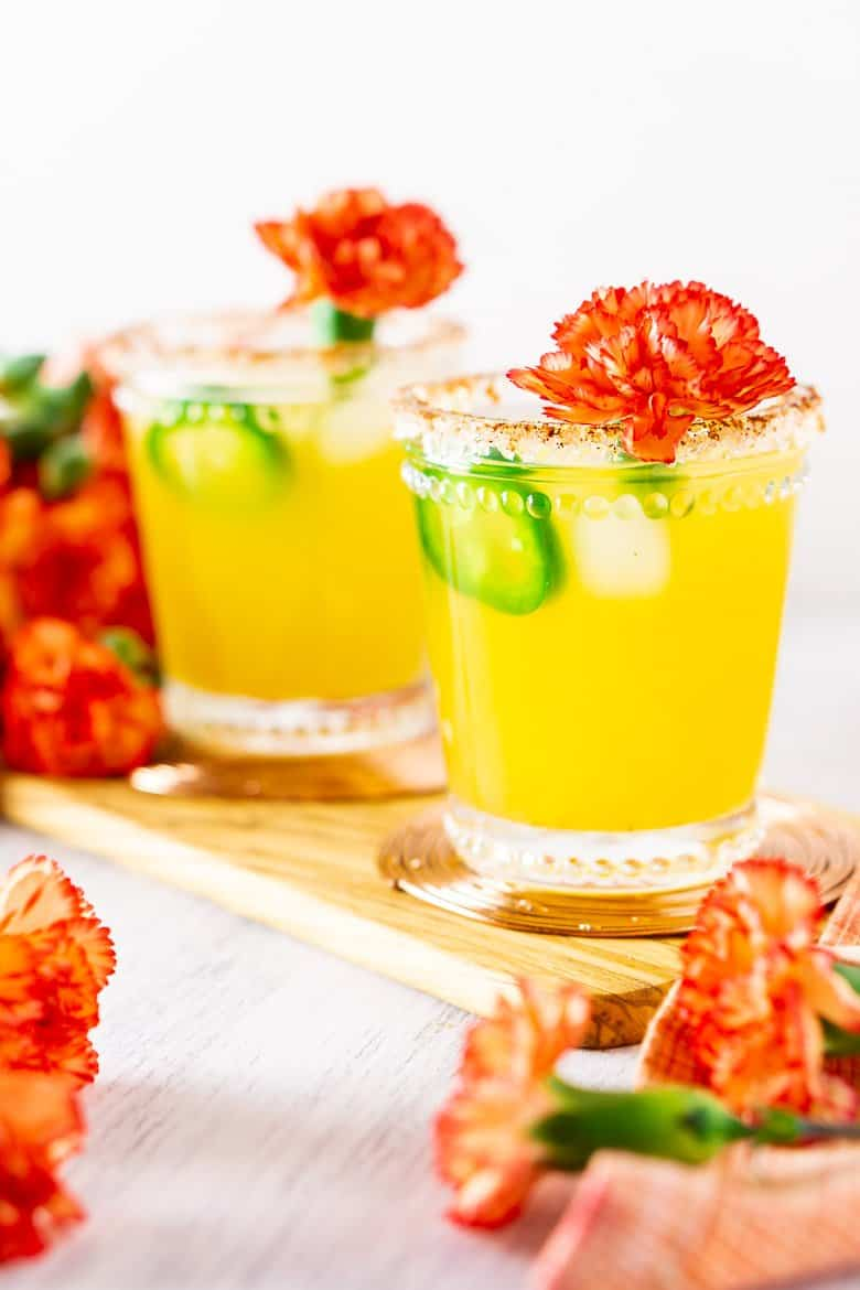 An upfront look at two jalapeno-mango margaritas with flowers.