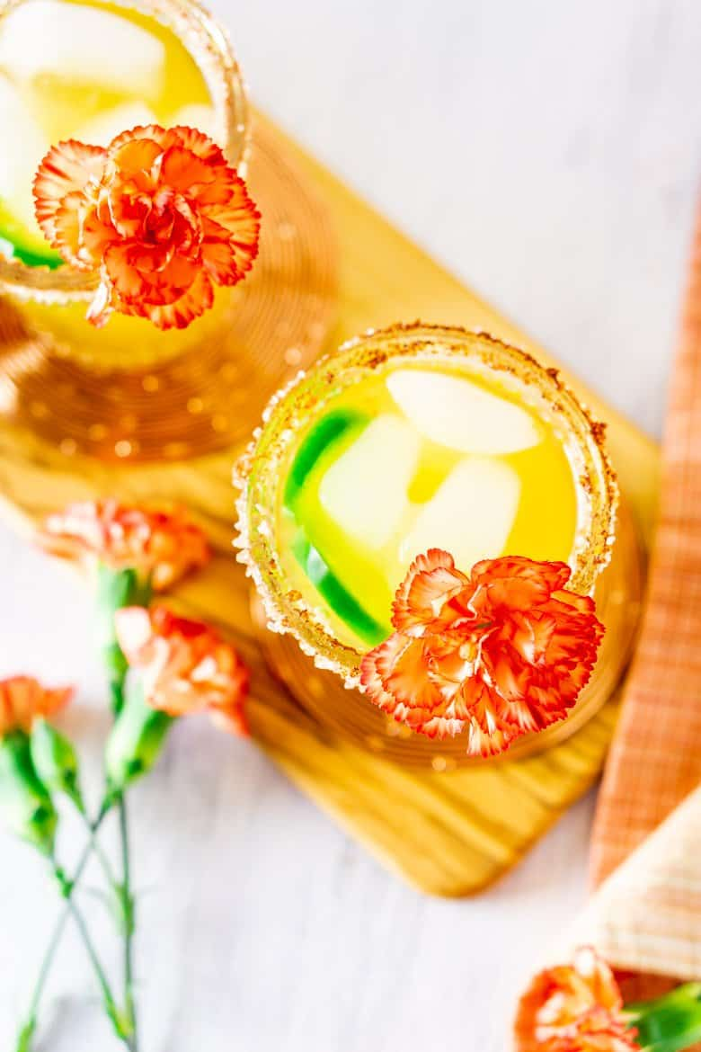 An aerial view of two jalapeno-mango margaritas on a wooden board.