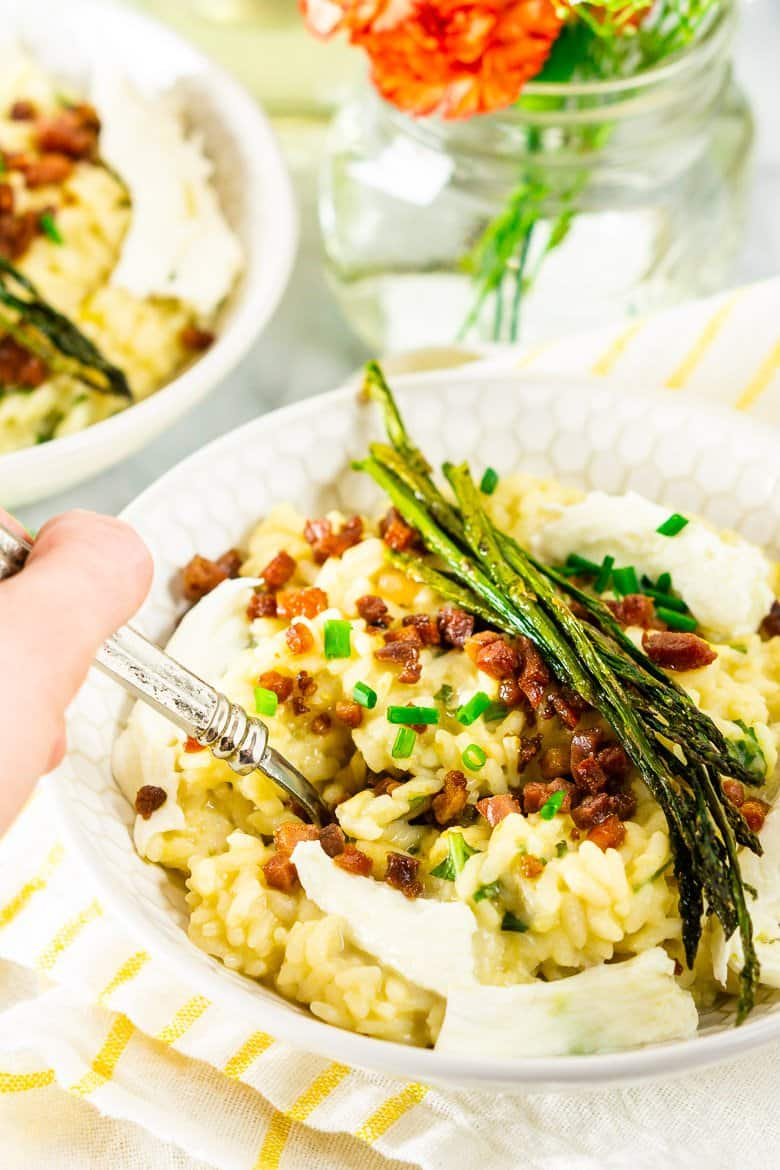 A hand with a spoon getting a bite of the spring risotto.
