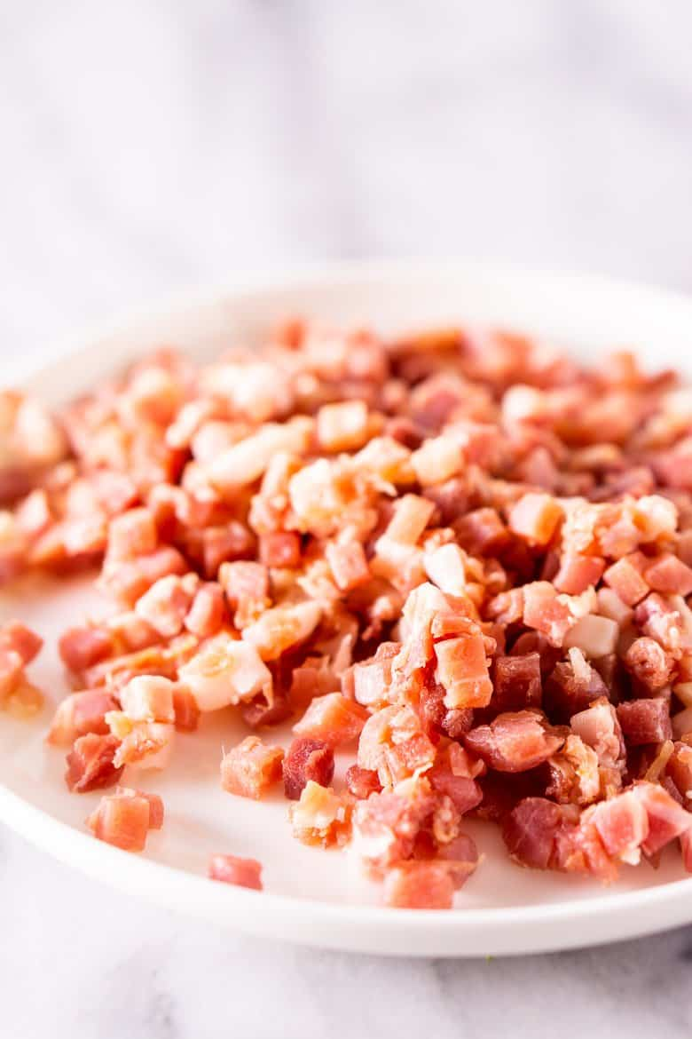A white plate with cubed prosciutto.