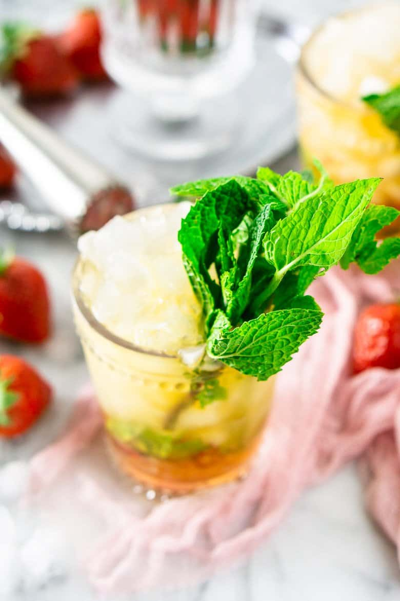 Looking into a glass of strawberry mint julep with a muddler in the background.