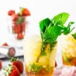 A strawberry mint julep with strawberries in the background.
