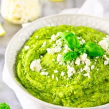 A bowl of feta-avocado pesto sauce with a jar of feta and lemon slices in the background.
