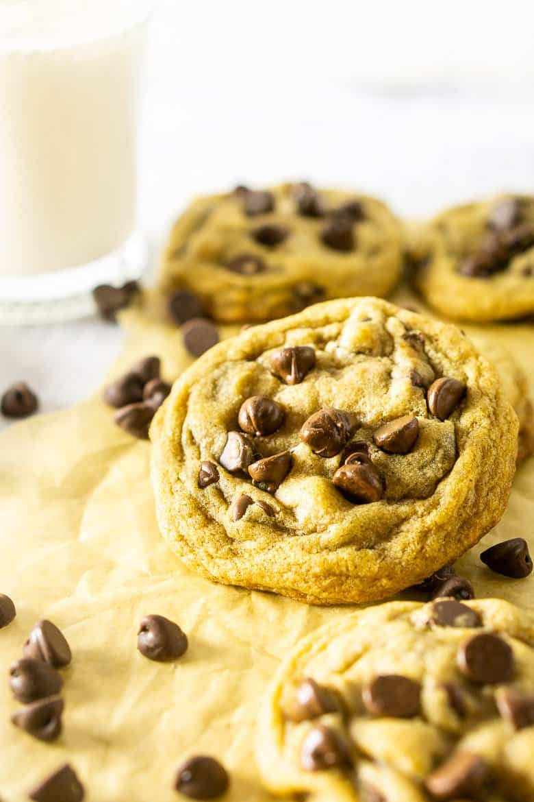 A brown butter chocolate chip cookie propped up with cookies surrounding it.