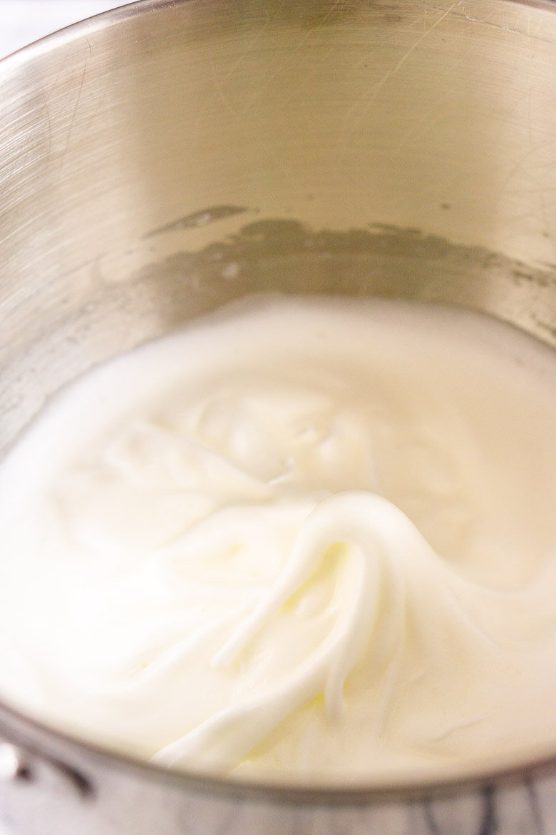 A bowl of egg whites beaten to soft peaks.