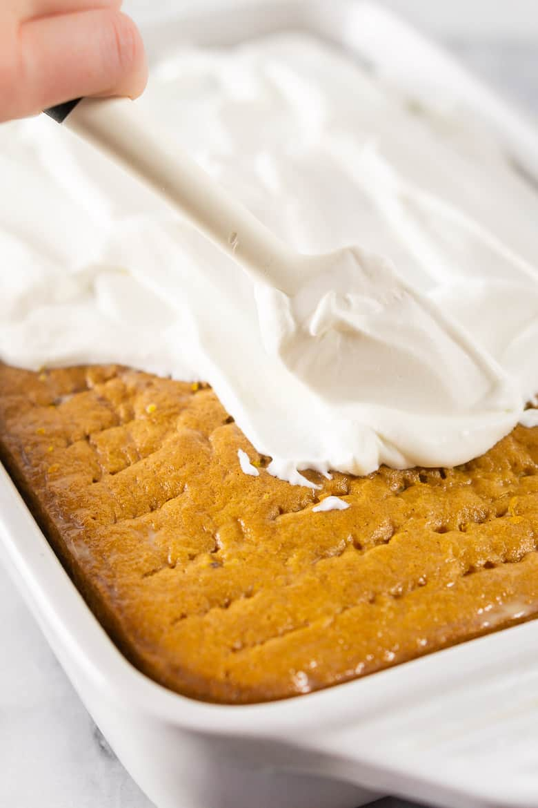 A hand spreading the whipped topping onto the spiced orange tres leches cake.