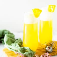 Two pineapple mimosas on a wooden board with flowers.