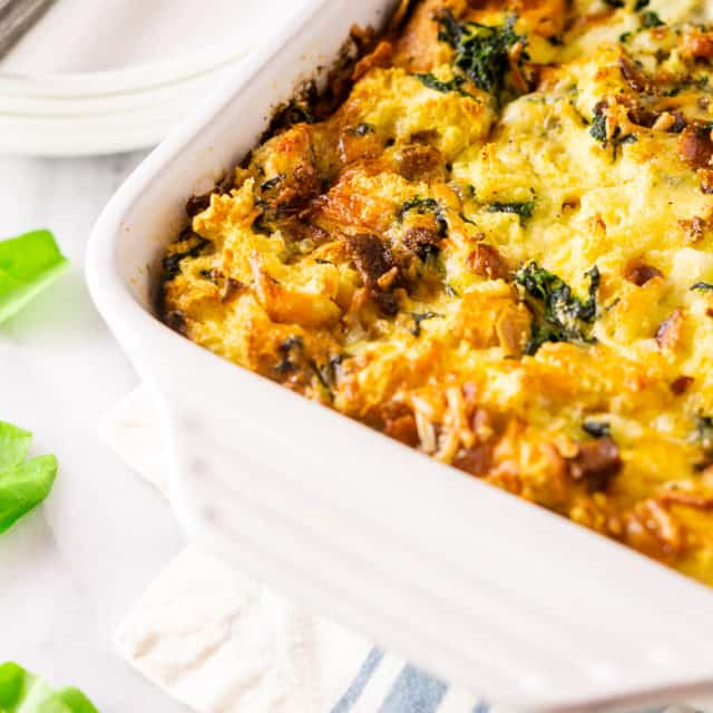A pan of cooked bacon, Gruyere and spinach strata on a napkin.