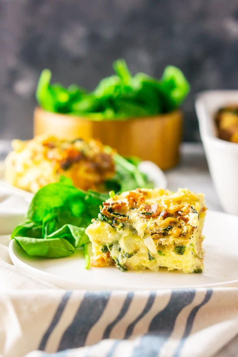 A front view of a piece of bacon, Gruyere and spinach strata with the pan in the background.